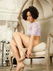 Curly-haired Pammie Lee bares her large tits and sweet ass on the chair.
