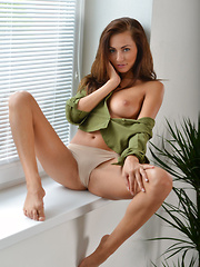 Top model Michaela Isizzu bares her trimmed pussy by the window.