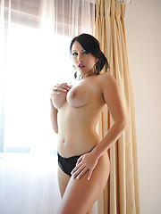 Nude brunette demonstrates her round ass and pretty tits