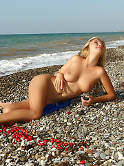 Gorgeous long haired blonde honey demonstrating her perfect body outdoors on the coast.